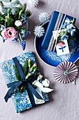 Presents wrapped in blue-and-white paper decorated with flowers and spruce sprigs
