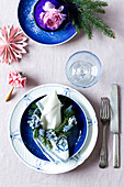 A blue-and-white place setting with napkin ring of grape hyacinths and a sprig of spruce