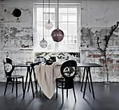 Schwarzer Tisch mit heller Tischdecke, Stühle und Glaskugellampen im Industrie-Ambiente