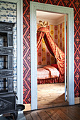 Blick ins Schlafzimmer mit Himmelbett und Tapete