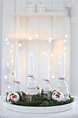 Tablett mit vier weißen Kerzen, Weihnachtskugeln und Tannenzweigen