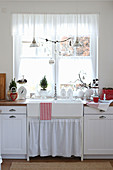 A white rural kitchen with a sink in front of the window