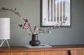 Sprigs of cherry plum blossom in a black vase on a sideboard