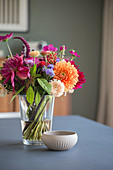 A bouquet of dahlia in a glass vase, and a porcelain bowl on a table
