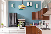 A breakfast counter in an open-plan kitchen with a light-blue wall
