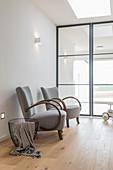 Zwei Sessel und Metallkorb vor verglaster Industrietüren in Loft-Wohnung