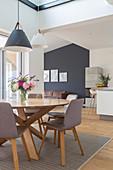 Runder Esstisch mit grauen Stühlen in offenem Wohnraum