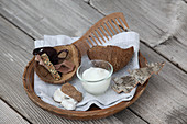Homemade coconut hair oil on a wooden tray with coconut shell and comb