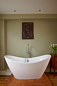 Free-standing bathtub in the bathroom with an olive green wall