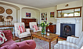 Upholstered armchair and coffee table in front of the fireplace in an English country house