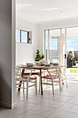 Dining table and classic chairs on tiled floor next to terrace windows