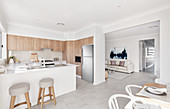 Island counter and bar stools in bright kitchen with dining area in foreground