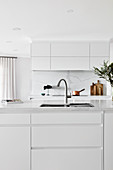 Island counter with integrated sink in elegant white kitchen