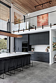 Long kitchen island with bar stools and black kitchen cabinets below gallery level