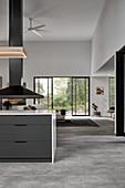 Kücheninsel, darüber Abzugshaube in offenem Wohnraum
