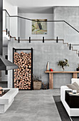 Stacked firewood against side wall in high-ceilinged interior