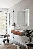 Hängewaschtisch und Spiegel neben Duschkabine