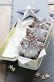 Gluten-free, homemade chocolate stars with powdered sugar in a metal tin
