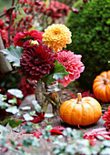 Autumn table decorated with dahlias, pumpkins, ivy and maple leaves