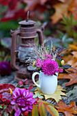 Spirea, dahlias, autumn leaves and rusty lantern on garden table