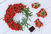 Tying a wreath of pyracantha berries