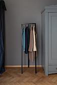 Kleiderständre neben grau-blauem Kleiderschrank im Flur
