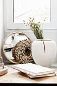 Vase mit Trockenblume, Kranz, Spiegel und Notizbücher