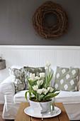 Schale mit weißen Tulpen auf dem Couchtisch im Wohnzimmer