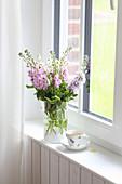 Strauß aus Levkojen und Mutterkraut am Fenster
