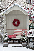 Arbour bench in winter with a berry wreath and red and white cushions