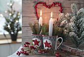 Kerzen und Zweigen in Weihnachtstassen mit Hagebuttenherz