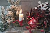 Kerze in Backförmchen auf Holzstern, Christbaumkugel, Tannenbäumchen und Hagebutten