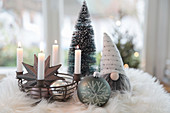 Metal basket as an Advent wreath with Christmas tree baubles, pewter star, gnomes and tiny trees