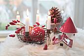 Eisenkorb als Adventskranz mit rot-weißen Christbaumkugeln, Hagebutten, Keramikhäuschen und Zapfen