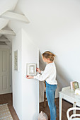 Blonde woman hanging a mirror on the wall