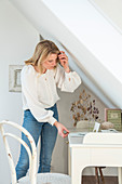 Blonde woman standing next to the desk in attic room
