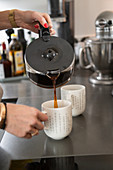 Pouring filter coffee from a glass jug into a mug