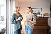 Freundinnen trinken Kaffee im Wohnzimmer vor Klavier