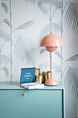 Table lamp, book and brass mug on a chest of drawers in front of wallpaper