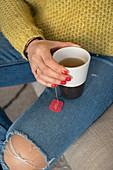 Woman's hand holding mug of tea with tea bag