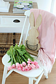 Pink tulips and wooden bunny on a white chair
