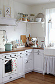 Kitchen with wooden worktop and pastel-coloured utensils