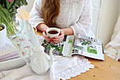 Teapot, magazine and woman's hands holding cup of tea