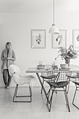 Dining table and classic chairs in a bright room: woman standing against the wall