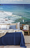 Double bed, bedside table and pendant lamp in front of a photo wallpaper of the sea