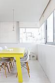 Gelb lackierter Esstisch und weiße Klassikerstühle in hellem Raum