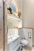 View of wash basin with base cabinet and toilet in high-ceilinged bathroom