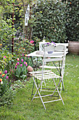 Table and chair next to spring bed of tulips