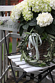 White hydrangea in a basket with a wreath of olive leaves