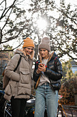 Two women in autumn clothing looking at a smartphone